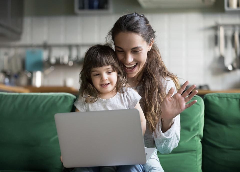 Mum and daughter sitting on couch with computer